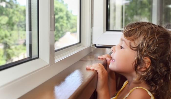 pretty smiling little girl on balcony, look from window